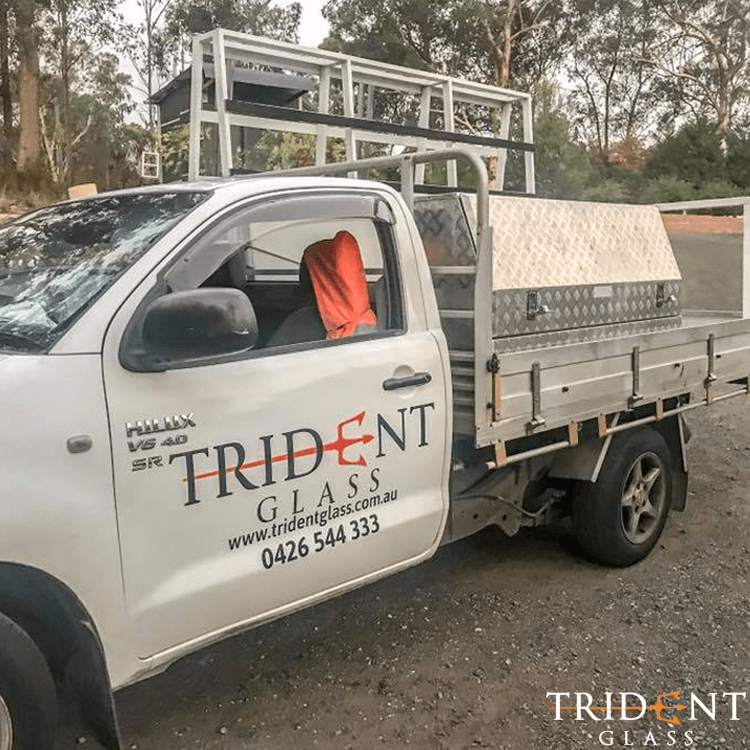 A Trident Glass branded ute, loaded with glass panels